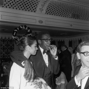 """Daily Mail caption: """"Up in smoke: Cosby hangs out with his arm around his wife, Camille Hanks, at a Four Tops concert at the Cocoanut Grove nightclub in LA. He often left her at home when he went carousing."""""""